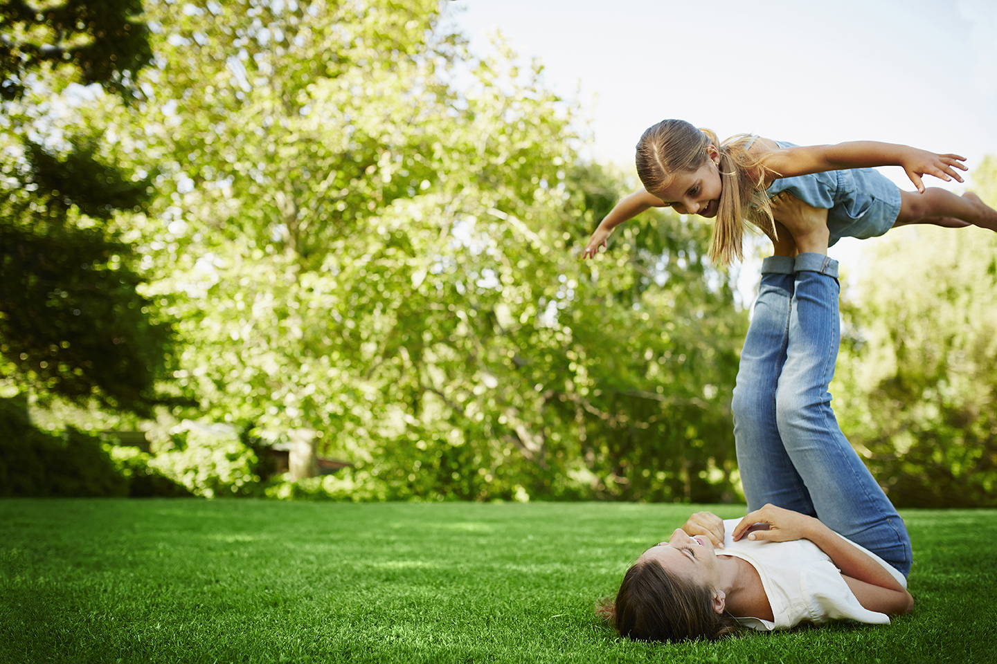 Mother lifting daughter with legs in park