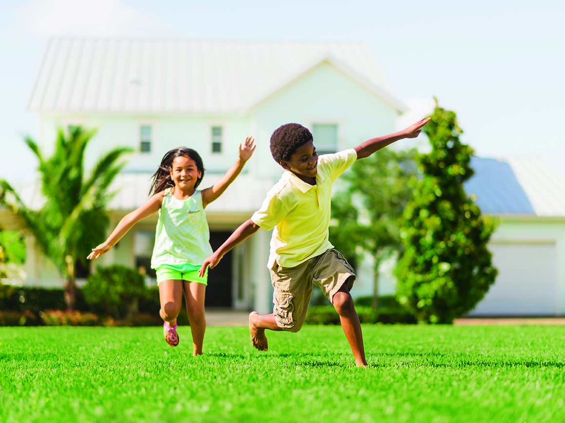 Girl and boy playing on front yard