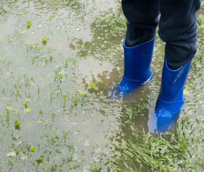 child in blue boot standing in flooded yard